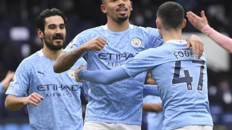 Manchester Citys Gabriel Jesus (M) feiert mit seinen Teamkollegen Ilkay Gündogan (l) und Phil Foden (r) seinen Treffer zum 1:0.