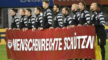 Die österreichische Nationalmannschaft hält vor Spielbeginn ein Banner mit der Aufschrift «Menschenrechte schützen» hoch.