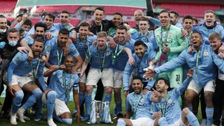 Die Spieler von Manchester City lassen sich mit dem Liga-Pokal fotografieren.
