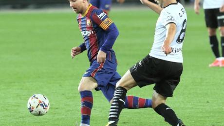 Barcelonas Lionel Messi (l) im Duell mit Valencias Carlos Soler.