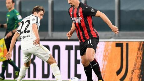 Juves Federico Chiesa (l) versucht Milans Zlatan Ibrahimovic vom Ball zu trennen.