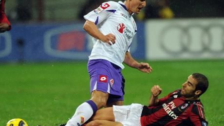 Gianluca Comotto (l) von Florenz wird von AC Mailands Mathieu Flamini attackiert.
