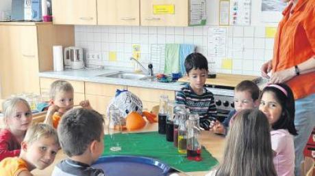 Erzieherin Ursula Wrona-Michl baut mit den Kindern der Schulvorbereitenden Einrichtung Balzhausen und Paula eine Glasorgel mit verschieden hoch gefüllten Flaschen mit buntem Wasser.