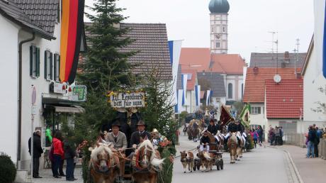 """""""Hl. Leonhard bitt für uns"""", steht auf einem der Gespanne, die durch Balzhausen fahren. Die Prozession zu Pferde lockt dieses Jahr zahlreiche Zuschauer auf die Straßen – im gegensatz zu den Vorjahren bei trockenem Wetter."""