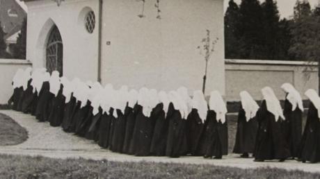 Das Bild zeigt Novizinnen auf dem Weg zum Friedhofsbesuch.