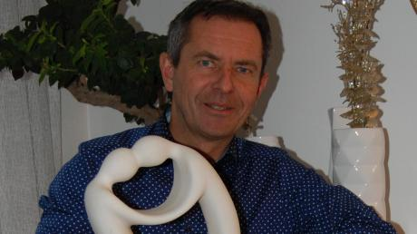 Gerhard Weiß in seinem Wohnzimmer mit einer Skulptur, die zeigt, wie Politik aus seiner Sicht sein sollte.