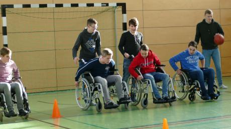 Schüler der zehnten Klassen beim Rollstuhl-Hindernisparcours in der Sporthalle.