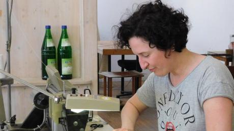Anke Vorbrugg sitzt an der Nähmaschine in der WfbM St. Simpert und näht Nasen-Mund-Abdeckungen. Sonst arbeitet sie in der Gruppenleitung der Förderstätte. Vormittags betreut sie noch eine Person und nachmittags hilft sie beim Nähen, das sie einst in der Schule gelernt hat und sonst nur in Faschingszeiten für ein Kostüm tut.