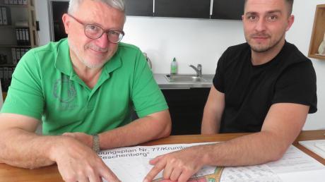 """Michael Wiedemann und sein Sohn Maximilian zeigen auf den Bereich, wo die neue Hackschnitzelheizzentrale für das neue Baugebiet """"Am Reschenberg"""" entstehen soll. Diese Anlage könnte auch noch weitere Bereiche versorgen."""