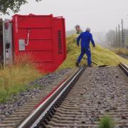 Mit Schaufeln müssen Männer Tonnen von Mais aus einem umgekippten Anhänger von der Bahnline Krumbach Mindelheim zwischen Aletshausen und Hohenraunau schaufeln.