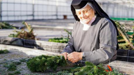 Schwester M. Arntraud CSJ in ihrem Element in der Klostergärtnerei Ursberg, hier beim Kränzebinden.