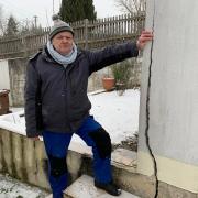 Manfred Schierle zeigt den meterlangen Riss in der Wand seines Gartenhauses. Hat eine Neigung der im Hintergrund zu sehenden Friedhofsmauer den Schaden verursacht?