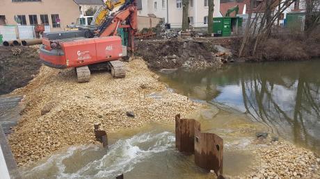 Baumaßnahmen in der Thannhauser Christoph-von-Schmid-Straße: Um die Spundwände im Flussbett verankern zu können, musste für das Bohrgerät ein Damm aufgeschüttet werden.