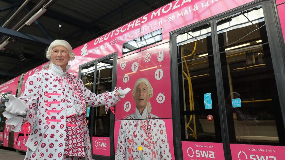 d55ab1bb684644 Eine Straßenbahn in pink und weiß mit einem Leopold Mozart im modernen  Gewand (Wolfgang Niederzoll) fährt nun durch die Stadt.