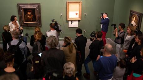 """Banksys Bild """"Love is in the Bin"""" hängt jetzt zwischen Alten Meistern in der Staatsgalerie Stuttgart."""
