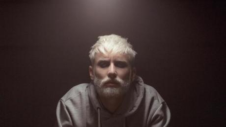 Tom Neuwirth jetzt mit blondem Bart und Kurzhaarfrisur wirbt für das Musikprojekt Wurst.