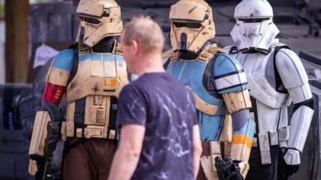 Als Sandtrooper verkleidete Mitglieder des Legion501 beobachten einen Besucher des Fanprojekts «Outpost One» mit Nachbildungen aus «Star Wars»-Filmen. Foto: Jens Büttner