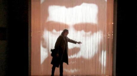 Eine Besucherin steht vor einem Kunstwerk, einem Streifenvorhang mit einem Porträt des französischen Konzeptkünstler Christian Boltanski. Foto: Sabine Glaubitz/dpa