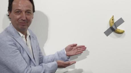 """Galerist Emmanuel Perrotin zeigt auf das Kunstwerk """"Comedian"""" von Maurizio Cattelan auf der Art Basel in Miami."""