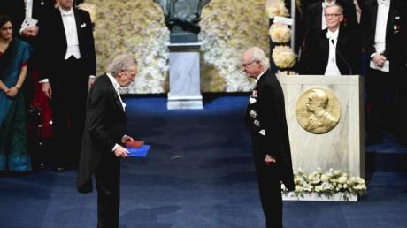 Peter Handke (l) erhält den Nobelpreis von König Carl XVI. Gustaf von Schweden in der Konzerthalle in Stockholm.