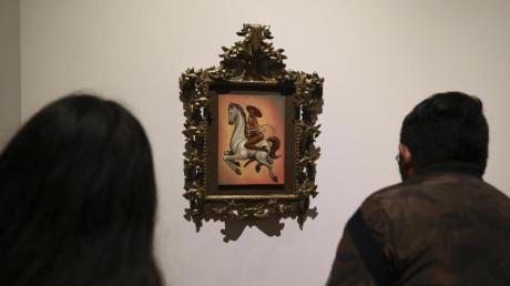 Besucher beobachten ein Gemälde, auf dem der mexikanischen Nationalheld Emiliano Zapata nackt und mit hochhackigen Schuhen dargestellt wird.