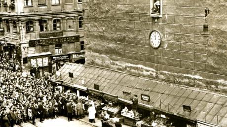 """Turamicheletag 1930: Die """"sieben Lädla"""" am Fuß des Perlachturms bieten ein üppiges Warenangebot auf ausgeklappten Theken."""