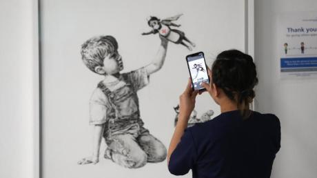 """Eine medizinische Mitarbeiterin fotografiert das erst kürzlich erschienene Banksy-Kunstwerk mit dem Titel """"Game Changer""""."""