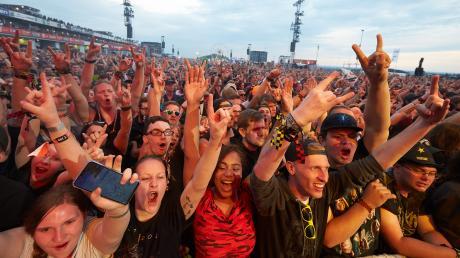 """Musikfans jubeln auf dem Gelände des Festivals """"Rock am Ring"""" 2019. Zum zweiten Mal muss das Festival wegen der Corona-Pandemie abgesagt werden."""