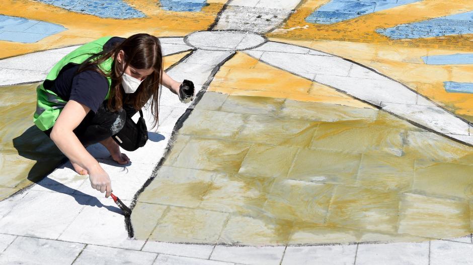 Kreativer Protest: Eine Aktivistin von Fridays For Future malt in Essen ein Windrad, während die Hauptversammlung von RWE stattfindet.