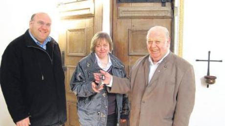 Schlüsselübergabe in St. Peter und Paul in Windach: Adolf Schulz (rechts) gibt sein Mesneramt an Christine Gall ab, links im Bild Pfarrer Robert Neuner.