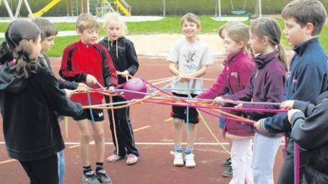 """Großen Spaß machte das Geschicklichkeitsspiel """"Ei im Nest"""", bei dem die Kinder mit lose geknoteten Seilen einen Ball über eine bestimmte Distanz transportieren mussten."""