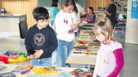 Interessiert blicken die Schüler auf die vielen Bücher, die auf den Tischen ausliegen.