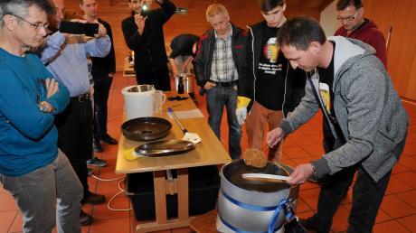 Im Rotter Pfarrheim zeigten Martin Pfuff (rechts) und Grenor Glassmann (links daneben) wie man Bier braut, hier füllen sie die Maische in den Läutertopf.