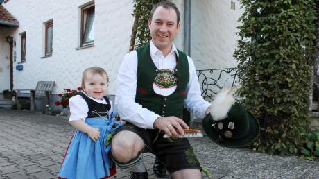 Martin Probst, Vorsitzender D'Windachtaler Hofstetten, bürstet schon mal seinen Hut mit dem Adlerflaum. Die kleine Magdalena trägt zwar auch schon die Vereinstracht, darf aber nicht mit auf die Wiesn.