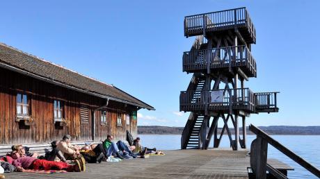 Auch im Winter oder im Frühjahr nutzen Uttinger Bürger die Gelegenheit, die ersten wärmenden Sonnenstrahlen auf der Holzterrasse des Strandbades beim Sprungturm zu genießen.