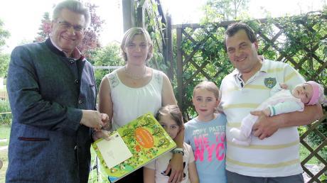 Hurlachs Bürgermeister Wilhelm Böhm überreichte an Sabrina und Martin Gerum eine Karte und ein Wimmelbuch für die kleine Marie. Mit dabei sind auch die Töchter Katharina und Juliane.