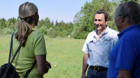 Harold Löffler (Mitte) ist als Naturschutzwächter unterwegs. In der Hurlacher Heide traf er ein Ehepaar, das eine seltene Blume fotografieren wollte.
