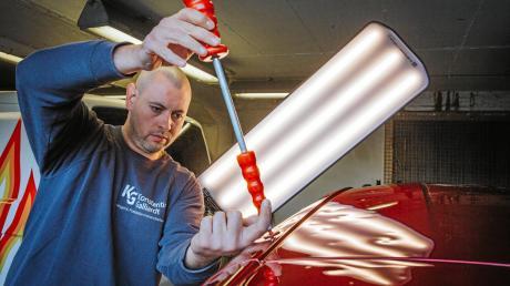Konstantin Galliardt ist Kfz-Mechaniker und verbringt die Sommer immer dort, wo es gehagelt hat. Derzeit ist er in Utting und arbeitet die Folgen des Pfingstunwetters ab, indem er Autos ausbeult und Dellen beseitigt.