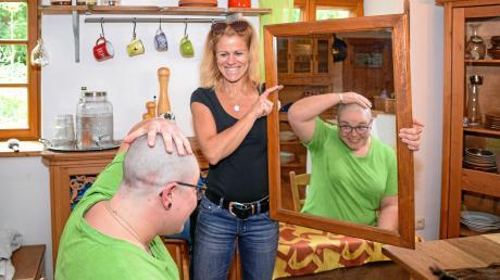 Spenderin Franziska Ziegler sieht sich zum ersten Mal ohne Haare im Spiegel, den Initiatorin Sara Eisenbarth hält.