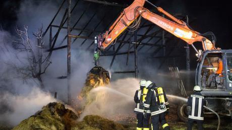 Einsatz bei Reichling: Feuerwehrleute löschten das in der völlig ausgebrannten Scheune gelagerte Stroh ab.