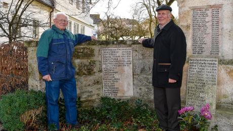 Siegfried Lang (links) und Ludwig Ziegler am Kriegerdenkmal in Oberigling. Eine Tafel erinnert an die Opfer eines Bombenangriffs, der sich am 16. Februar 1945 ereignet hat.