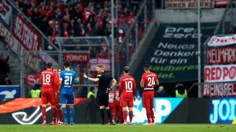 Schiedsrichter Christian Dingert (Mitte) spricht mit Spielern von Hoffenheim und München.