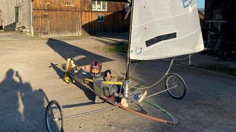 Die Not macht erfinderisch: Dießener Segler haben aus alten Surfbrettteilen und einem Laufrad einen kleinen Optimisten für Landfahrten gebaut.