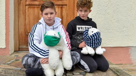 Tobias (13, links) und Lenny (9) Rieb haben ihre Kuscheltiere (Eisbär und weißer Tiger) mit Mund-Nasen-Masken vor die Haustür gestellt. Damit wollen die Kinder darauf aufmerksam machen, dass ihnen die lange Trennung von Freunden und Klassenkameraden immer stärker zu schaffen macht.
