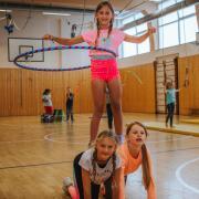 Lea (mit Reifen) und ihre Freundin Amelie (oranges Shirt) und Lucy haben Spaß beim Zirkusprojekt.