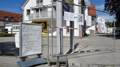 Das große Wohn- und Geschäftshaus in Greifenberg, in dem es zwei Mal gebrannt hat, ist mit Bauzäunen abgeriegelt. Die mutmaßliche Brandstifterin sitzt in Untersuchungshaft.