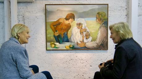 """Margarete Bartsch (links) und Waltraud Vogel tauschen anlässlich der Retrospektive zum 100. Geburtstag Erinnerungen über die Malerin und Autorin Ingeborg Weigand aus. Im Hintergrund """"Am Strand"""", Öl auf Leinwand, 1980."""