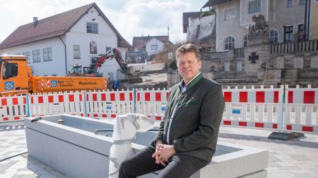 Bürgermeister Andreas Braunegger sitzt am Brunnen des neuen Rathausplatzes.