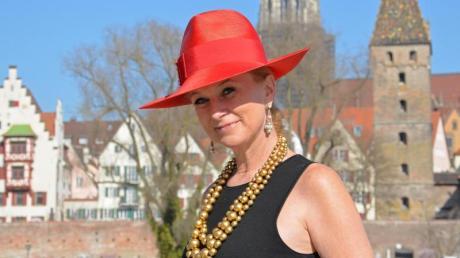 Schick angezogen und trotzdem Flagge zeigen: Personal Shopperin Sonja Grau trägt ein schwarzes Kleid zu rotem Hut und goldener Kette. Foto: Jasmin Grau
