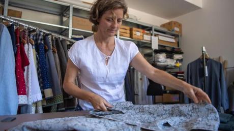 Caroline Herrmann-Lauenstein, Mode-Designerin, kombiniert auf einem Tisch in einer Werkstatt ihrer Manufaktur verschiedene Stoffe zu einem Design. Foto: Lino Mirgeler/dpa